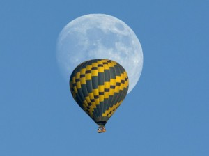 Hot air balloon floats past an almost full rising moon on a warm fall evening near Encinitas, California