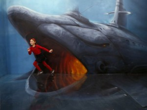 A girl runs past an art installation depicting a shark at the Museum of Optical Illusions in St. Petersburg