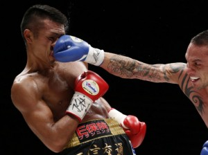 Challenger Perez of Argentina punches the champion Uchiyama of Japan during their WBA boxing super featherweight title bout in Tokyo